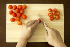 Chopping Cherry Tomato on Cutting Board Stock Photography