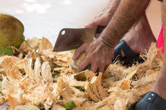 Chopping coconut by knife. Chopping coconut by big knife Stock Photo