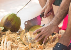 Chopping coconut by knife. Chopping coconut by big knife stock images