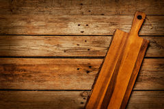 Chopping (cutting) board on rustic planked table Stock Photos