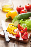Chopping fresh vegetables cucumber tomatoes pepper and salad lea Stock Image