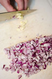 Chopping garlic. Cook chopping garlic and red onion on a white  board Stock Images