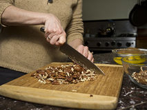 Chopping pecans. A woman chops up pecans for a pecan pie recipe Royalty Free Stock Photography