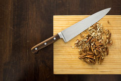 Chopping pecans, from above. Chopped pecans with knife on a bamboo cutting board, from above Stock Photos