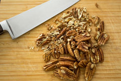Chopping pecans, detail. Chopped pecans with knife on a bamboo cutting board, detail shot Stock Images
