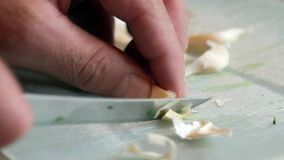 Chopping and peeling garlic with knife on cutting board - Organic cooking concept stock video