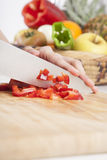 Chopping red pepper on wood plank Stock Photography