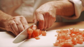 Chopping tomatoes on cutting board closeup shots stock footage