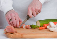 Chopping vegetables. Slicing vegetables on a wooden chopping board Stock Photos