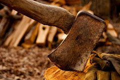 Chopping Wood. With axe and gloves focused in foreground and stack of chopped woood blurred in background Stock Images