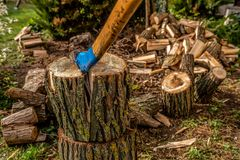 Chopping wood to the fireplace for heating on cold winter days. Chopping wood to the fireplace for fuel on cold winter days. An old strong ax can handle the royalty free stock photos