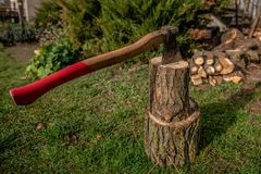 Chopping wood to the fireplace for heating on cold winter days. Chopping wood to the fireplace for fuel on cold winter days. An old strong ax can handle the royalty free stock photo