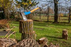 Chopping wood to the fireplace for heating on cold winter days. Chopping wood to the fireplace for fuel on cold winter days. An old strong ax can handle the royalty free stock photography