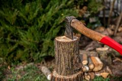 Chopping wood to the fireplace for heating on cold winter days. Chopping wood to the fireplace for fuel on cold winter days. An old strong ax can handle the royalty free stock image