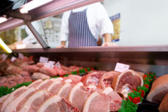 Chops in butcher`s shop, butcher in background, mid section Stock Photo