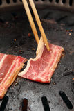 Chopstick holding sliced beef in grill. Chopstick holding a piece of sliced beef, laying it to sizzle on the grill Stock Image