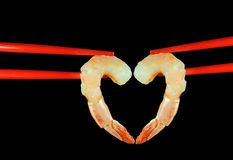 Chopstick love. Two raw shrimps held together in chopsticks forming a heart symbol of love Royalty Free Stock Photography