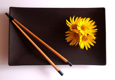 Chopstick Still Life. Simple modern-style still life of chopsticks, plate and flowers stock photo
