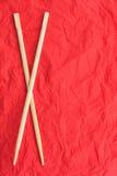 Chopsticks βάζουν σε μια κόκκινη πετσέτα Στοκ Εικόνες