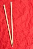 Chopsticks βάζουν σε μια κόκκινη πετσέτα Στοκ εικόνες με δικαίωμα ελεύθερης χρήσης