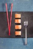 Chopsticks και δίκρανο με τα σούσια στο μαύρο πιάτο Στοκ εικόνα με δικαίωμα ελεύθερης χρήσης