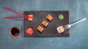 Chopsticks και δίκρανο με τα σούσια στο μαύρο πιάτο Στοκ εικόνες με δικαίωμα ελεύθερης χρήσης