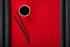 Chopsticks και κύπελλο με τη σάλτσα σόγιας στο χαλί βαμβακιού Στοκ Εικόνες