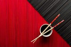 Chopsticks και κύπελλο με τη σάλτσα σόγιας Στοκ Εικόνες