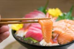 Chopsticks με sashimi σολομών με μικτό τεμαχισμένο sashimi ψαριών επάνω Στοκ Εικόνες