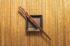 Chopsticks που τοποθετούνται καφετιά με την εξυπηρέτηση του πιάτου στο χαλί θέσεων Στοκ εικόνα με δικαίωμα ελεύθερης χρήσης