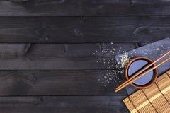 Chopsticks σουσιών και σάλτσα σόγιας στο μαύρο υπόβαθρο Τοπ άποψη με το διάστημα αντιγράφων στοκ φωτογραφίες