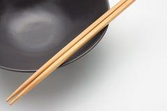 Chopsticks στο μαύρο πιάτο Στοκ εικόνα με δικαίωμα ελεύθερης χρήσης