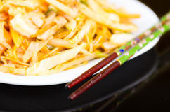 Chopsticks φιαγμένα από ξύλινο και που χρωματίζονται με το πράσινο χρώμα στην πλευρά του πιάτου νουντλς Στοκ φωτογραφίες με δικαίωμα ελεύθερης χρήσης