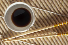 Chopsticks. Two japonese chopsticks on the bamboo mat and circular saucer Royalty Free Stock Photography