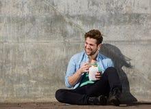 Ο εύθυμος νεαρός άνδρας που τρώει τα κινέζικα παίρνει μαζί τα τρόφιμα με chopsticks Στοκ Εικόνες