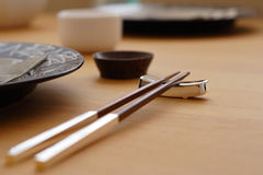 Chopsticks. Wood & chrome chopsticks on table set for dinner stock photography