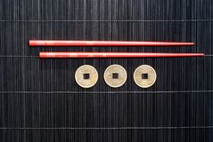 Chopsticks and Asian Coins Stock Image