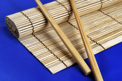 Chopsticks and bamboo mat. Isolated on blue Stock Images