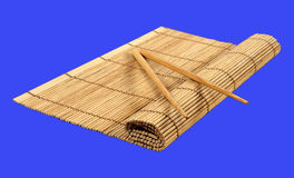 Chopsticks and bamboo mat. Isolated on blue Royalty Free Stock Photo