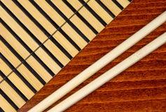 Chopsticks and bamboo mat Stock Photos
