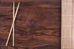 Chopsticks and bamboo napkin. Chopsticks and folded bamboo napkin on a wooden background Royalty Free Stock Images