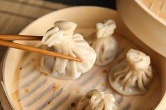 Chopsticks with baozi dumpling over bamboo steamer stock photos