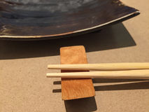 Chopsticks and black plate Royalty Free Stock Images