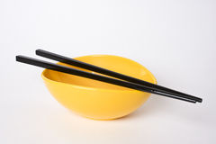 Chopsticks with bowl. 2 back chopsticks placed neatly  over a eye catching Yellow colored blow … a vibrant combination Stock Photography