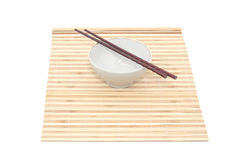 Chopsticks and bowl on bamboo mat. Isolated object Stock Photography
