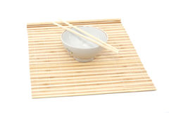 Chopsticks and bowl on bamboo mat Royalty Free Stock Images