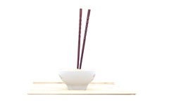 Chopsticks and bowl on bamboo mat. Isolated object Stock Photo