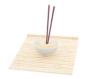 Chopsticks and bowl on bamboo mat. Isolated object Royalty Free Stock Photography