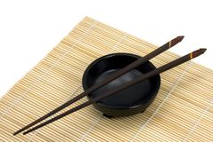 Chopsticks and Bowl - Horizontal. Chopsticks resting on black bowl with bamboo mat beneath - horizontal orientation stock images