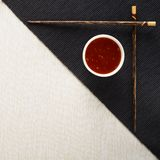 Chopsticks and bowl with sauce on table mat Stock Photo